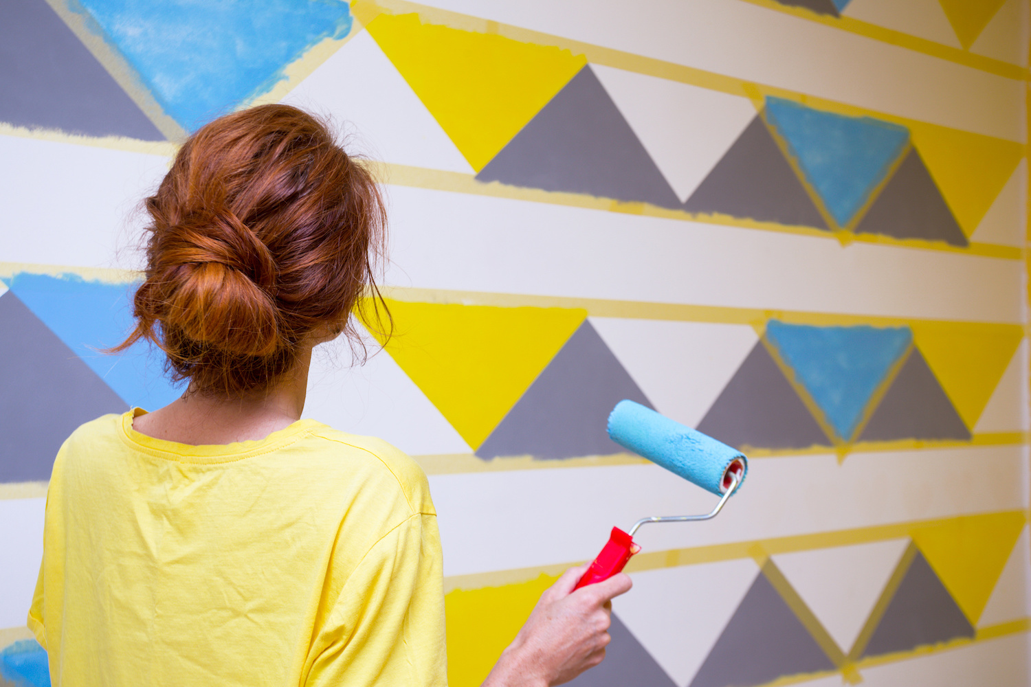 Interior Design. The girl paints the wall in geometric pattern.