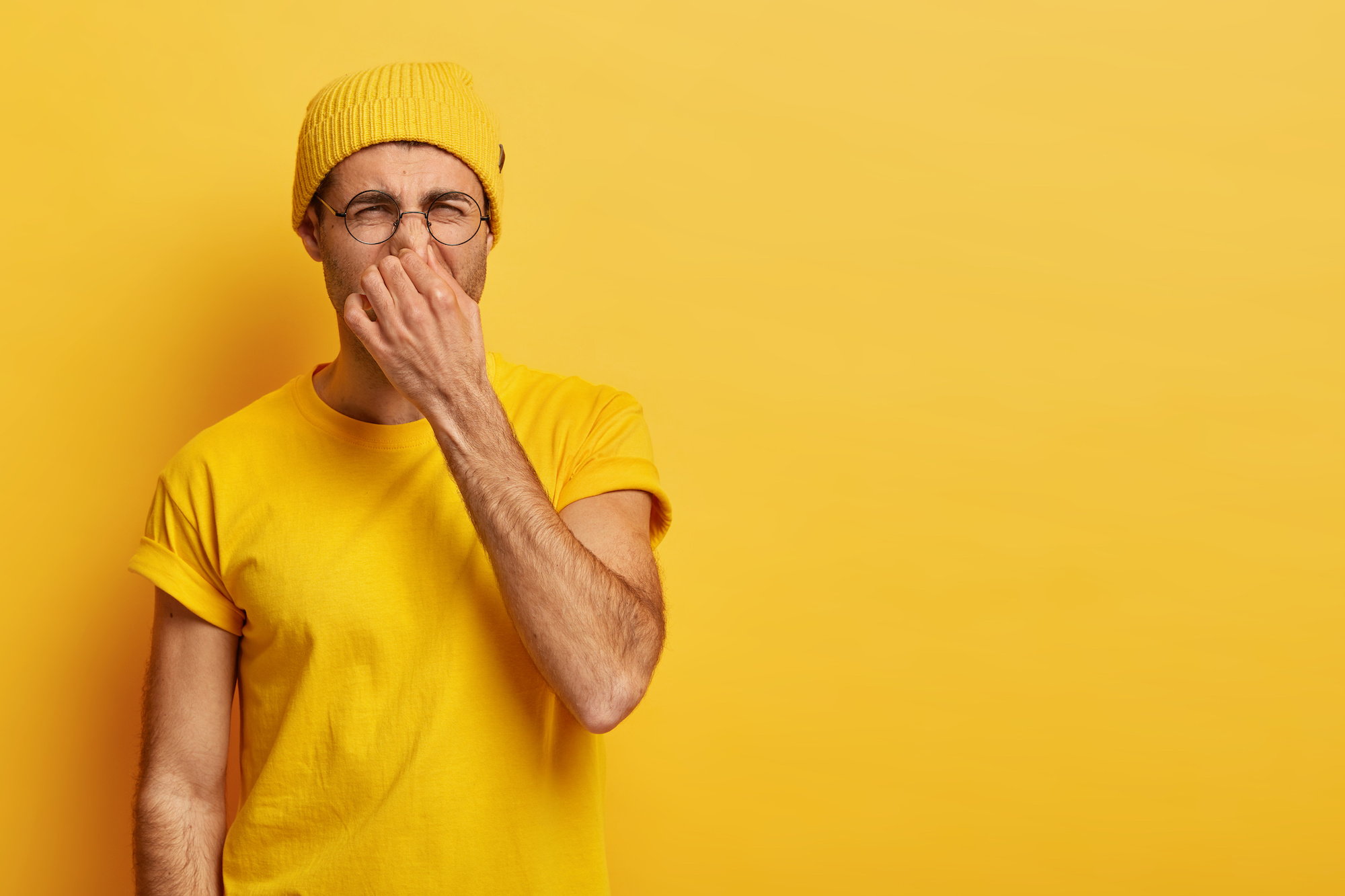 Disgusted young hipster pinches nose with fingers, looks in disgust as smells something stink, wears spectacles, yellow hat, t shirt, stands in stuido with blank copy space. Fie, unpleasant smell
