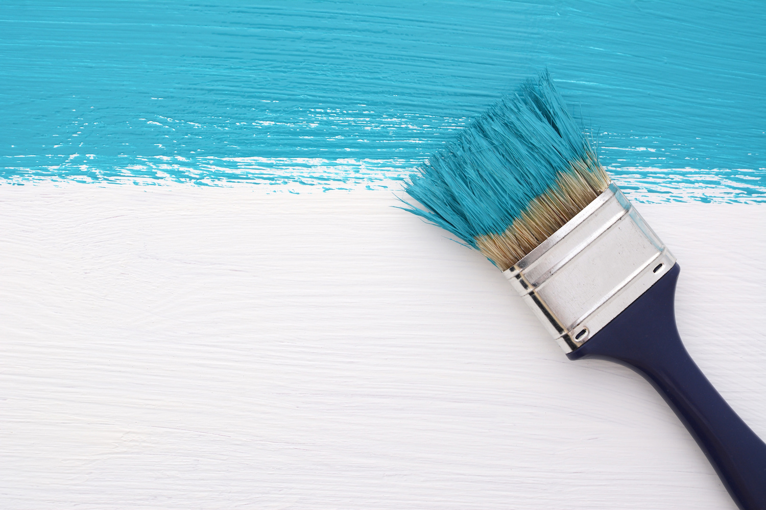 Horizontal stripe of turquoise paint with a dirty paintbrush on a white wooden board